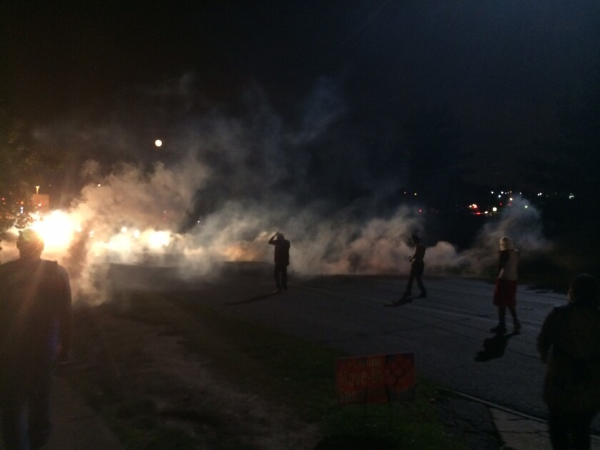 Demonstrators in Ferguson, Mo., scatter Monday night after police fired tear gas.