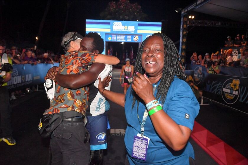Challenged triathlete Roderick Sewell, center, gets a hug at the finish line from Challenged Athletes Foundation co-founder Bob Babbitt while his mother, Marian Jackson, right, cries with relief at the 2019 Ironman World Championship in Hawaii on Oct. 12.