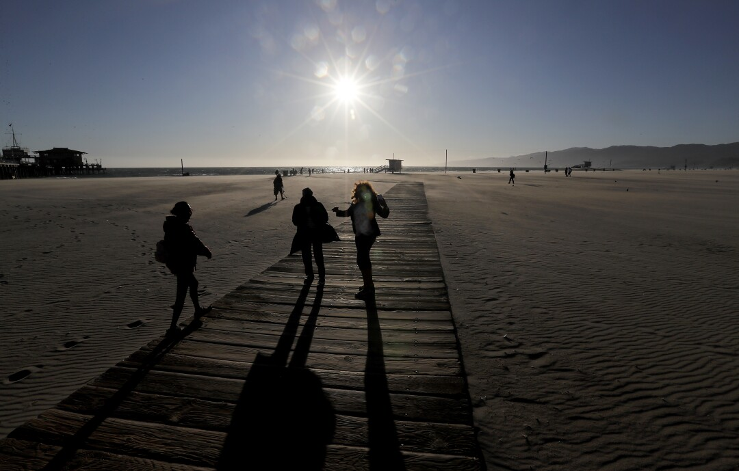 A handful of visitors walk on a largely deserted Santa Monica Beach.