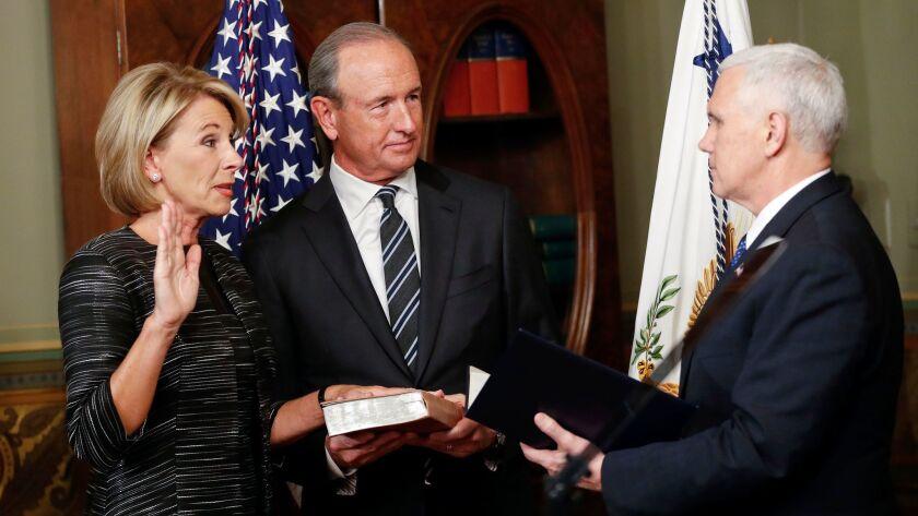 El vicepresidente Mike Pence, a la derecha, toma el juramento a la nueva secretaria de educación, Betsy DeVos. A ellos se les une Dick DeVos, esposo de la funcionaria. (Pablo Martínez Monsivais)