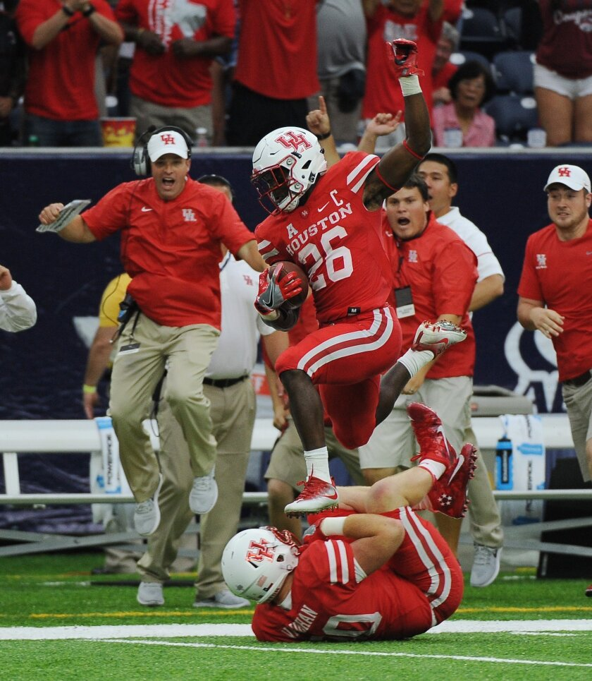 Houston cornerback Brandon Wilson (26) leaps over teammate Zach Vaughan (90) as he returns a missed field goal for a touchdown against Oklahoma in the second half of Houston's 33-23 victory in an NCAA college football game Saturday, Sept. 3, 2016, in Houston. (AP Photo/George Bridges)