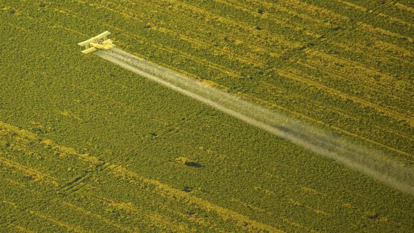 Spraying pesticides from a yellow plane, Northern California Aerial views of farmer's fields, USA -