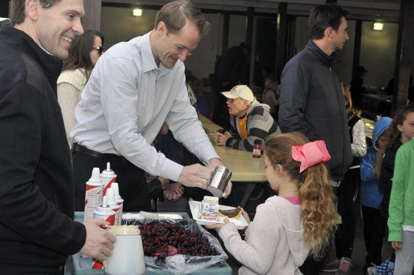 Dad's club member Jeff Capell helps with pancake toppings