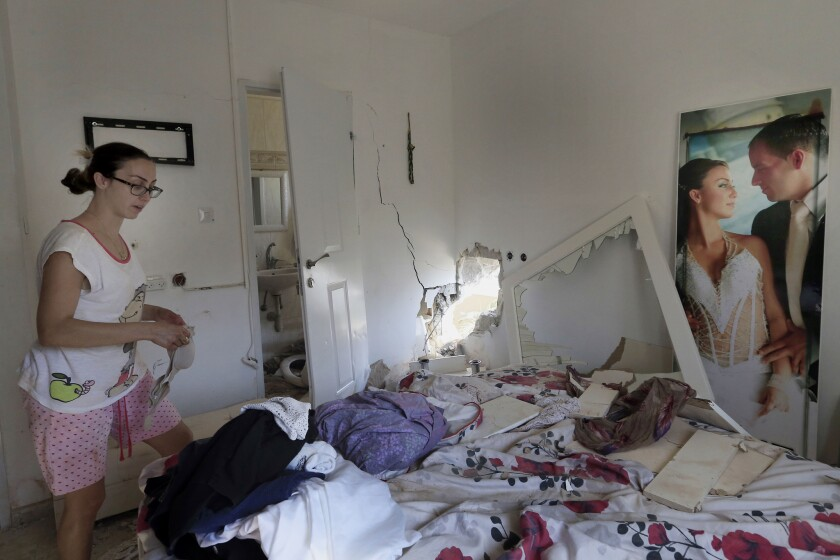 Tammy Giorno cleans up her bedroom in the southern Israeli town of Sderot after it was hit by a rocket fired by Palestinian militants in the Gaza Strip.