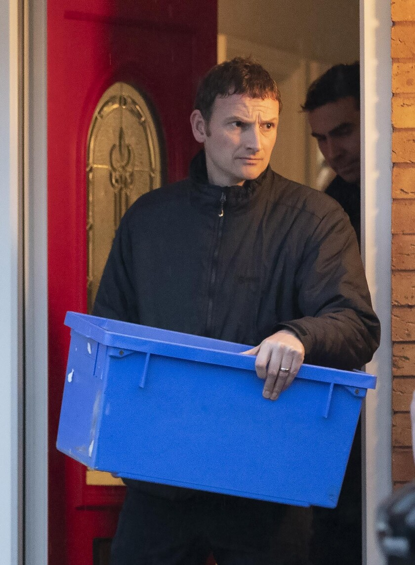 A police officer carrying an evidence box