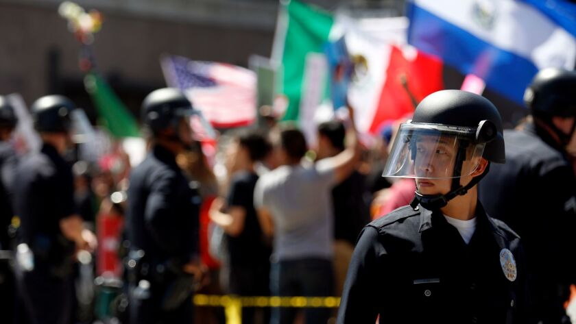 LAPD officers form a wall between pro- and anti-Trump protesters at 1st and Spring streets in downtown Los Angeles at the conclusion of separate May Day marches and rallies on Monday.