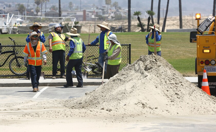 Workers clear sand and debris as a result of the flooding that occurred on Friday in Newport Beach.