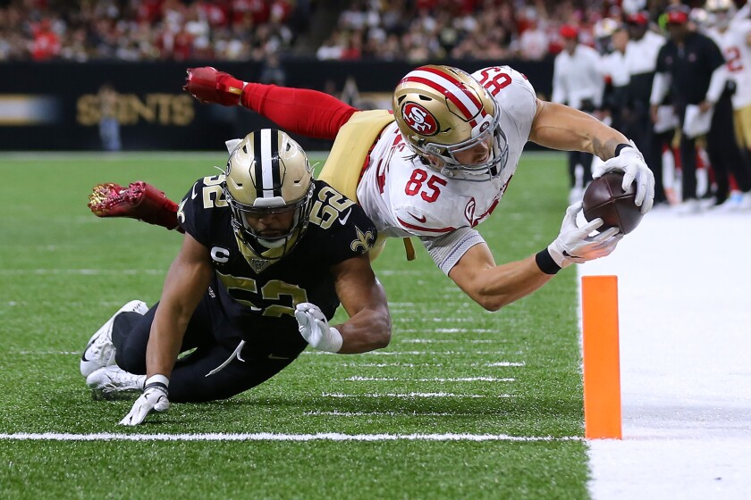 San Francisco 49ers tight end George Kittle scores a touchdown in front of New Orleans Saints linebacker Craig Robertson.