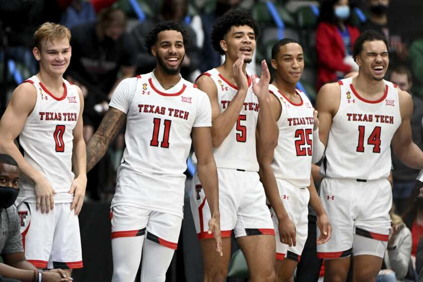 From left, Texas Tech guard Mac McClung (0), guard Kyler Edwards (11), guard Micah Peavy (5), guard Nimari Burnett (25), and forward Marcus Santos-Silva (14) react to a play in the second half of an NCAA college basketball game in Frisco, Texas, Saturday, Dec. 12, 2020. (AP Photo/Matt Strasen)