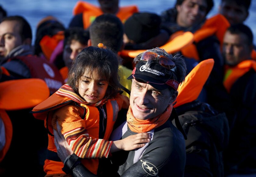 A German volunteer carries a Syrian refugee girl off an overcrowded raft after landing at a rocky beach in the Greek island of Lesbos, November 19, 2015.