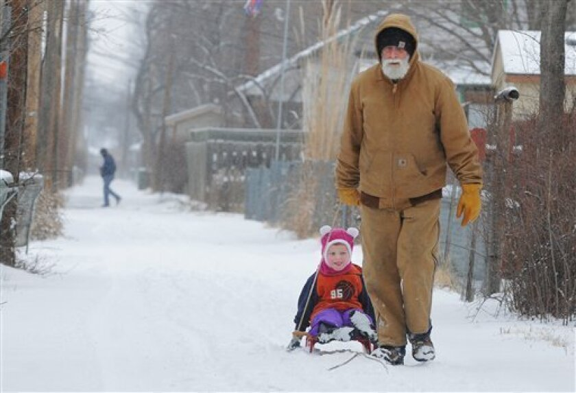 Ray Hughes pulls his grandson, Grant McMillen, 3, down an alley during a snow storm, Wednesday, Feb. 20, 2013 in Salina, Kan. Hundreds of snow plows and salt spreaders took to the highways of the nation's heartland Wednesday, preparing for a winter storm that could dump up to a foot of snow in some