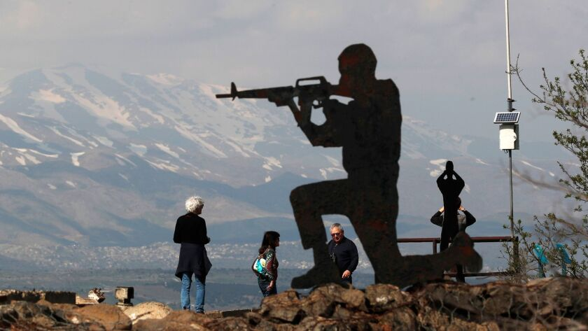 Israeli tourists stand near silhouetted cutout of an Israeli soldier at Ben Tal, next to the Israeli-Syrian border in the Golan Heights.