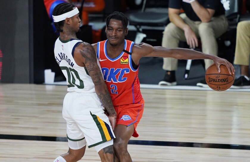 Oklahoma City Thunder's Shai Gilgeous-Alexander (2) drives into Utah Jazz's Jordan Clarkson (00) during the second half of an NBA basketball game Saturday, Aug. 1, 2020, in Lake Buena Vista, Fla. (AP Photo/Ashley Landis, Pool)