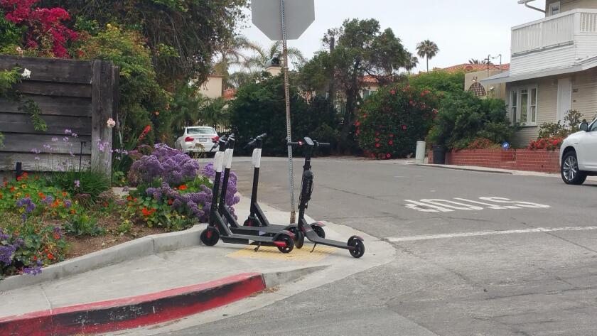 These scooters seen in La Jolla are completely blocking public sidewalks and curb access.
