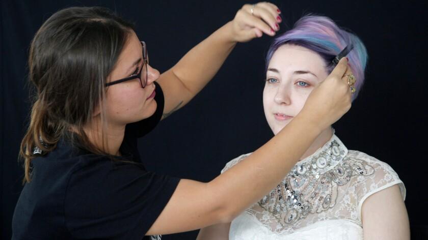 Makeup artist Amber Talarico pins back Kota Wade's hair.