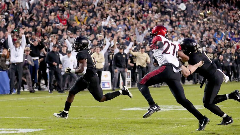 Kell Walker of the Army Black Knights carries the ball to score a two-point conversion against Kyree Woods of the San Diego State Aztecs in the fourth quarter of the Armed Forces Bowl.
