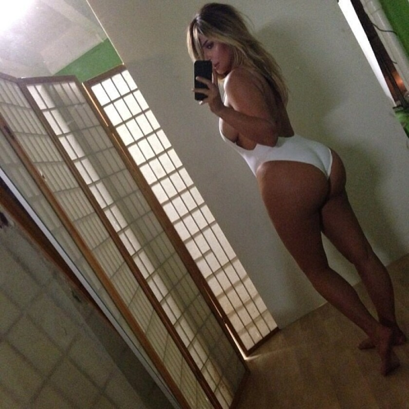 Kim Kardashian shows off her post-baby body with a self-portrait of herself in a revealing white swimsuit.