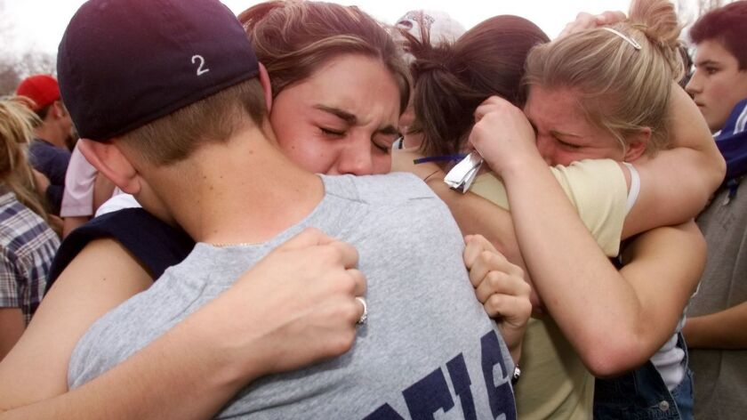 Students hug each other in the parking lot outside Columbine High School in Littleton, CO, the day after the infamous school shooting on April 20, 1999.