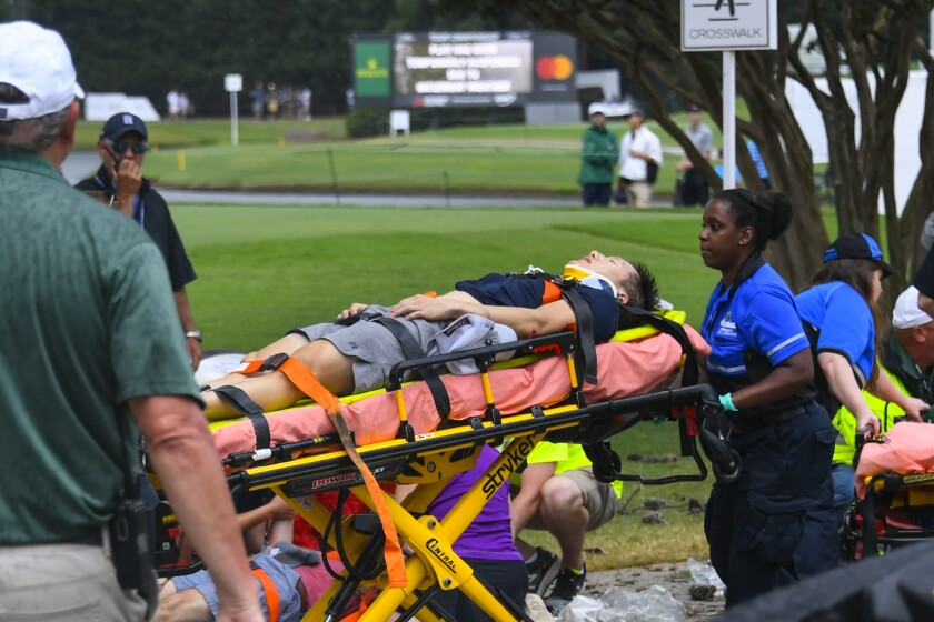 A spectator is moved to an ambulance after a lightning strike.