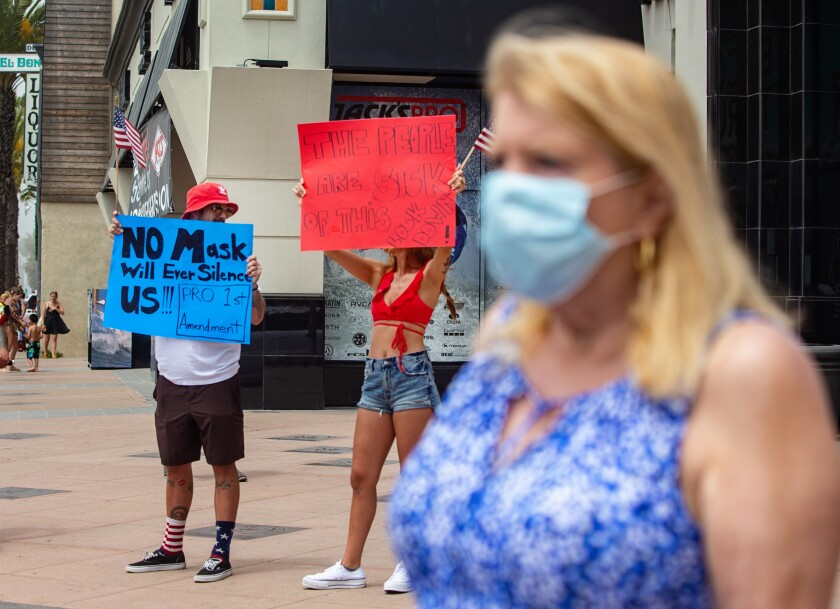 Demonstrators in Huntington Beach protest face mask rules.