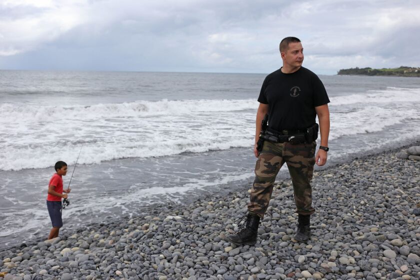 A police officer from Saint-Benoit's gendarmerie looks Saturday for debris from the ill-fated Malaysia Airlines Flight MH370 on Reunion Island in the Indian Ocean.