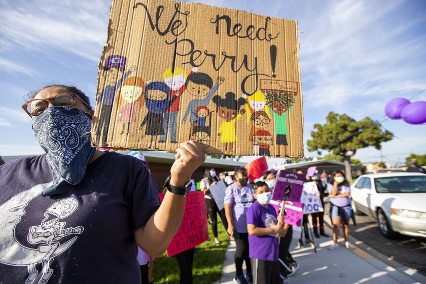 Diane Parras, an alumna of Perry Elementary School, holds a sign during a protest of the school's closure on Tuesday.