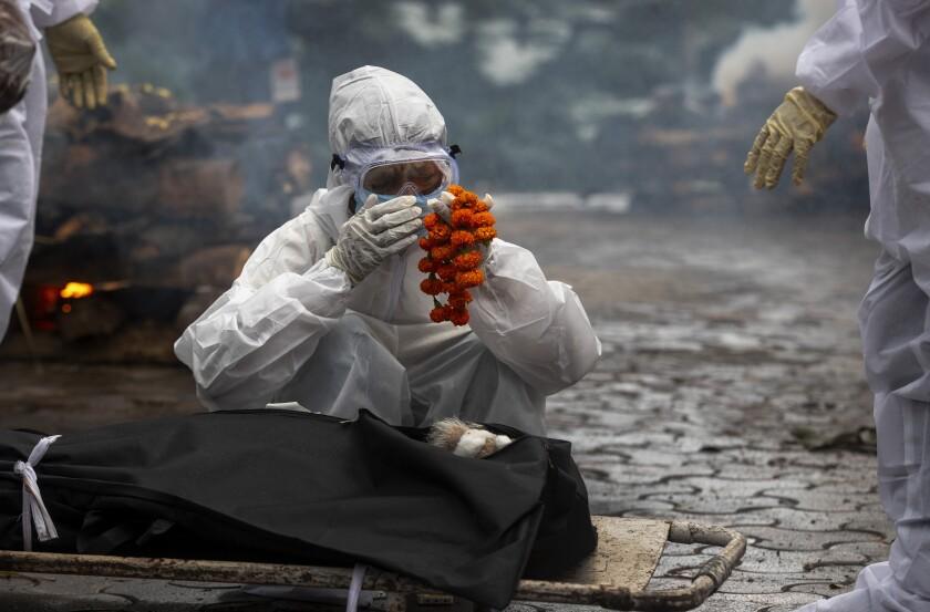 Fotografía de archivo del 2 de julio de 2021 de un familiar realizando los últimos ritos de la cremación de una víctima de COVID-19 en Gauhati, India. (AP Foto/Anupam Nath, Archivo)