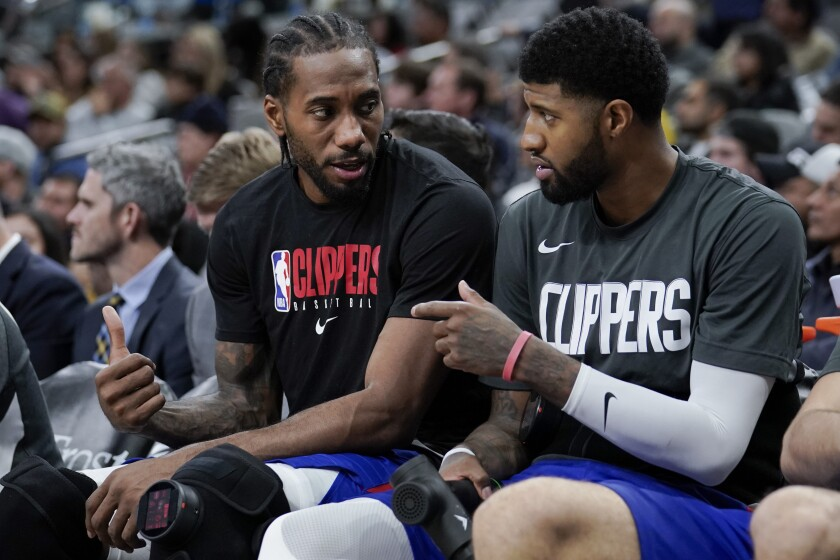 FILE - In this Dec. 21, 2019, file photo, Los Angeles Clippers' Kawhi Leonard, left, and Paul George talk on the bench during the second half of an NBA basketball game against the San Antonio Spurs in San Antonio. George and teammate Leonard can become free agents after the upcoming season. George could also sign a contract extension with the team. (AP Photo/Darren Abate, File)