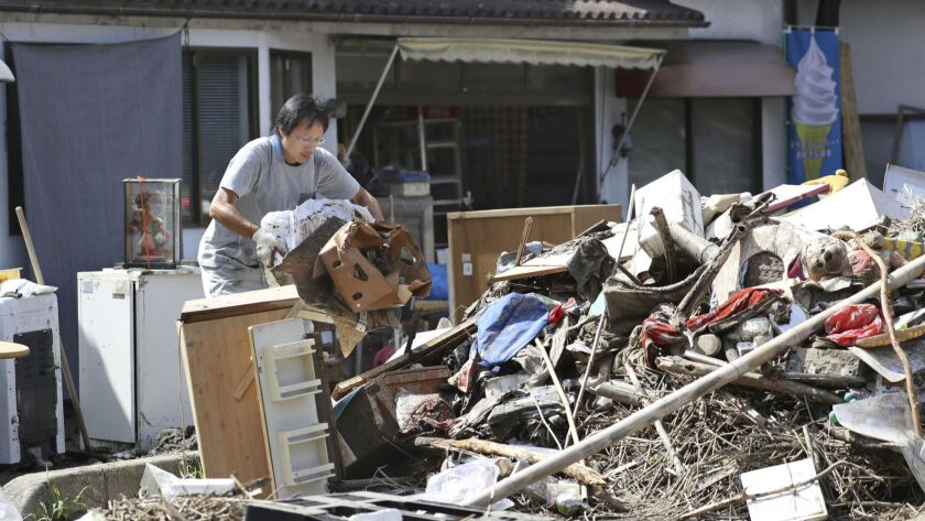 A man cleans debris caused by a heavy rain in Soja, Okayama prefecture, western Japan Monday, July 9