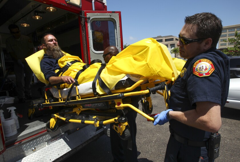 Paramedics Brian Christison, right, also a RAP paramedic, and William Moore move Richard Collins, 42, who is homeless and a chronic alcoholic, into an ambulance as they transport Collins to the UCSD Medical Center for an evaluation.