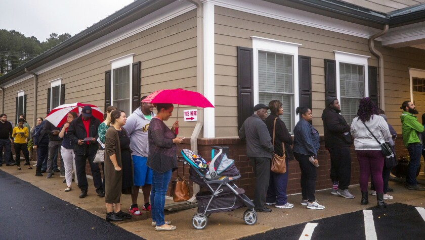 Miguelina Espinal (center) waits in the rain to vote at the Ivy Community Center with her 5-month-old son, Christian, on Tuesday in Durham, N.C. It's unknown if this voting location had ballot errors because of the humidity.