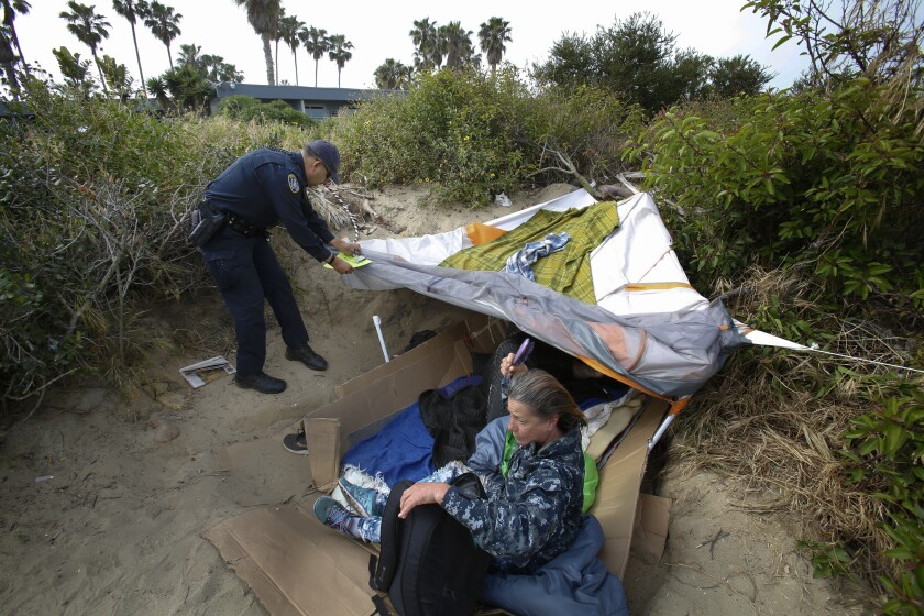 Officer Raul Flores with the San Diego Police Department, tapes a notice to a tent belonging to a homeless couple.