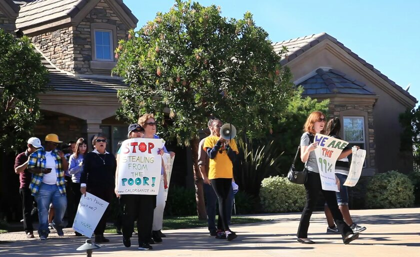 More than a dozen protestors went to the home of Jerry Rebel, Jack in Box executive to protest his support of referendum to overturn affordable housing linkage fees.