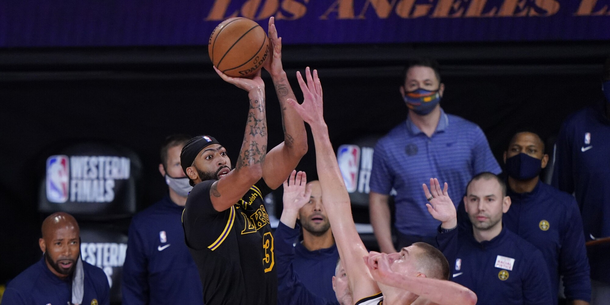 Lakers forward Anthony Davis shoots a three-pointer over Denver Nuggets center Nikola Jokic.