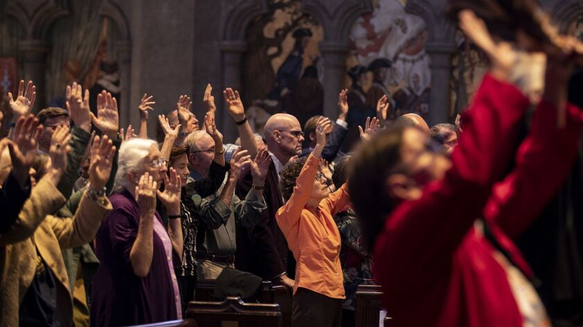 People raise their arms during an interfaith prayer during the Wondering and Commitment ceremony at Grace Cathedral to kick off the Global Climate Action Summit on Wednesday in San Francisco.