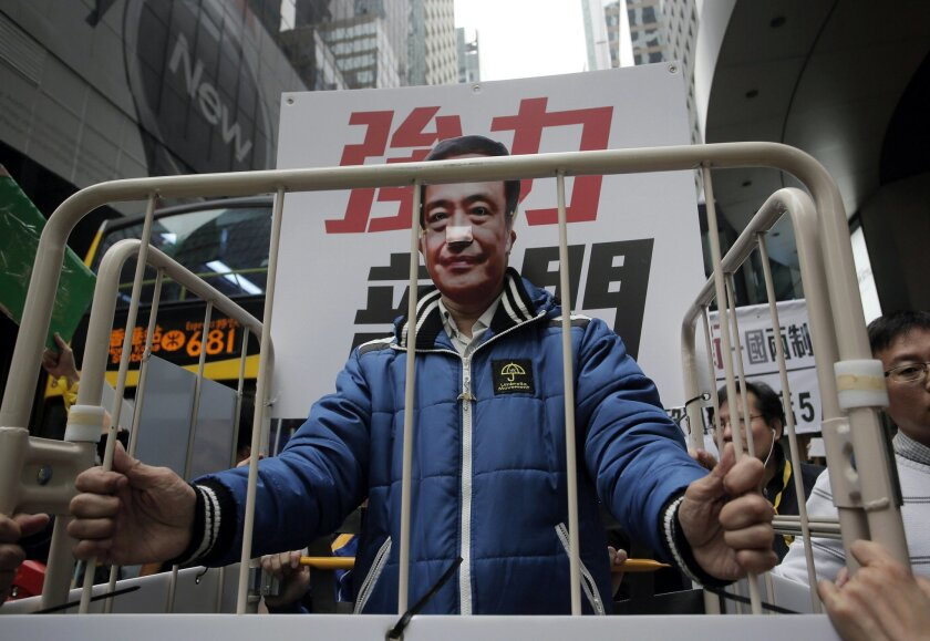 FILE - In this Jan. 10, 2016 file photo, a protester wearing a mask of missing bookseller Lee Bo sits in a cage during a protest against the disappearances of booksellers in Hong Kong. The wife of the missing chief editor of a publisher specializing in books banned in mainland China has told police