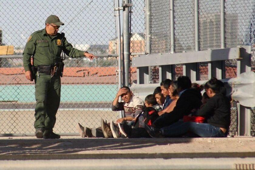 Un agente de la Patrulla Fronteriza da instrucciones a migrantes detenidos.