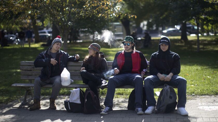 People smoke cannabis in a Toronto park on Wednesday, Oct. 17, 2018. Canada became the largest count