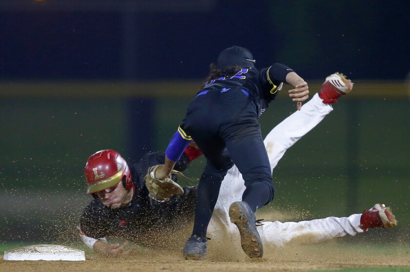 La Mirada shortstop Jimmy Blumberg catches Orange Lutheran infielder Tank Espalin trying to steal second base during a game at the Great Park in Irvine on Feb. 19, 2020.