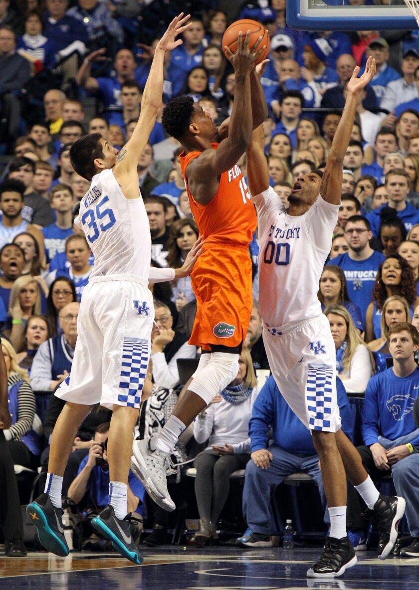 Florida's John Egbunu, center, shoots between Kentucky's Derek Willis (35) and Marcus Lee (00) during the first half of an NCAA college basketball game Saturday, Feb. 6, 2016, in Lexington, Ky. (AP Photo/James Crisp)