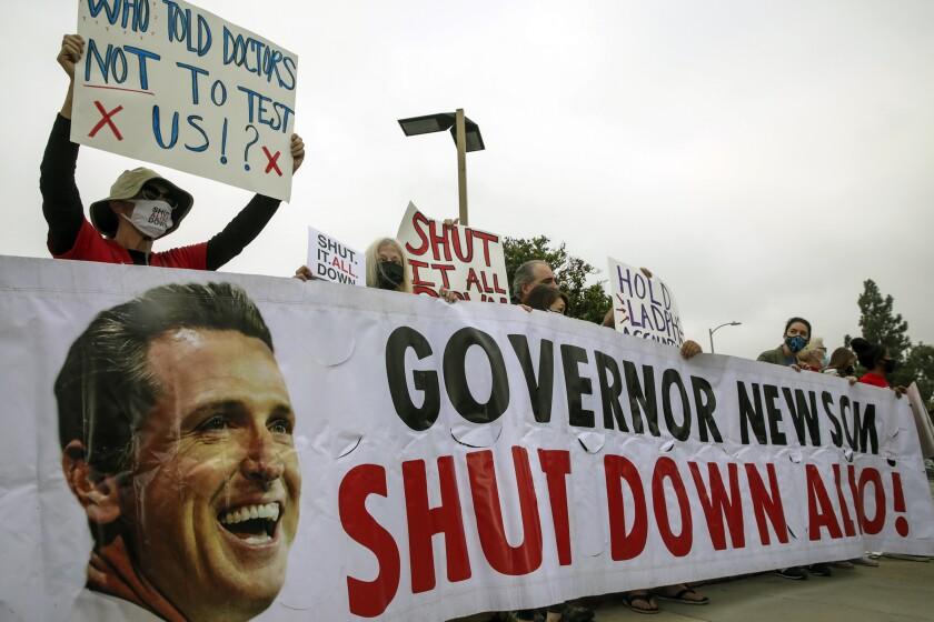 People holding signs stand behind a large banner with Gov. Gavin Newsom's face.