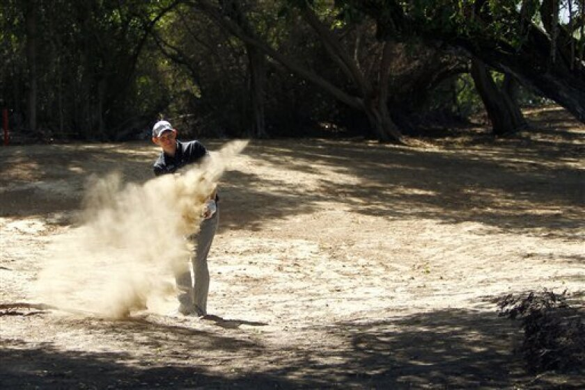 Stephen Gallacher of Scotland plays a ball on the dirt on the 2nd hole during the final round of the Dubai Desert Classic Golf tournament in Dubai, United Arab Emirates, Sunday, Feb. 3, 2013. (AP Photo/Kamran Jebreili)