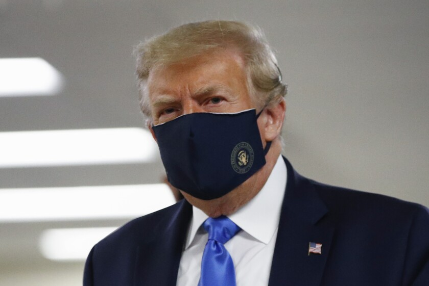 President Donald Trump wears a face mask during a visit to Walter Reed National Military Medical Center in Bethesda, Md.