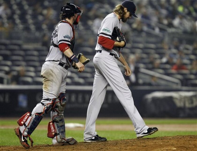 Boston Red Sox catcher Jarrod Saltalamacchia, left, interacts with relief pitcher Andrew Miller (30) in the 12th inning of their 4-3 loss to the New York Yankees in their baseball game at Yankee Stadium in New York, Tuesday, Oct. 2, 2012. (AP Photo/Kathy Willens)