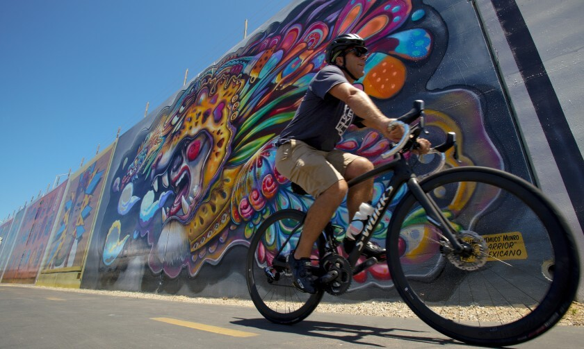 "Andy Hanshaw, executive director San Diego Bicycle Coalition, rides past a large mural along the Bayshore Bikeway in Chula Vista. The large mural by Guillermo ""Memuco"" Munro is one of eleven large wall murals painted by various artist along the bike route."