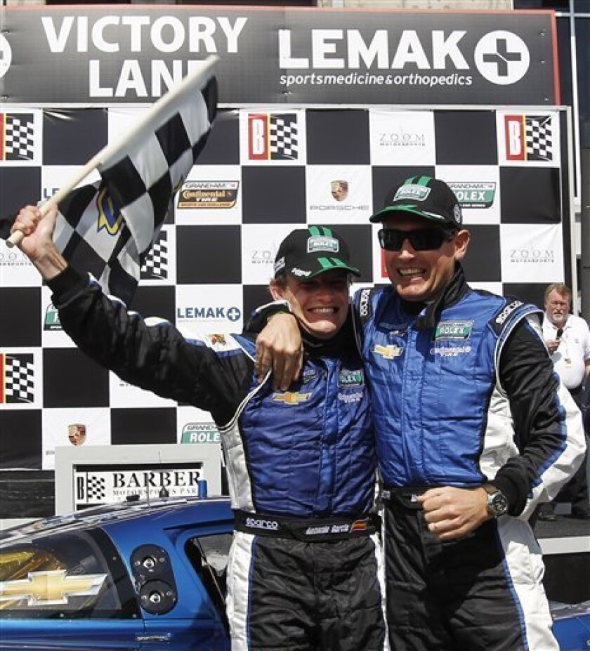 Antonio Garcia, left, and Richard Westbrook celebrate in victory lane after winning the Grand-Am Rolex auto race at Barber Motorsports Park on Saturday, March 31, 2012, in Birmingham, Ala. (AP Photo/Butch Dill)