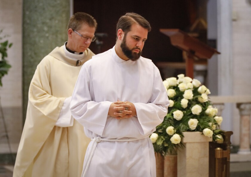 Marc Gandolfo, foreground, a candidate for the priesthood, assisting the Rev. Matthew Spahr, background, during Mass in the Immaculata, a church on the University of San Diego campus.