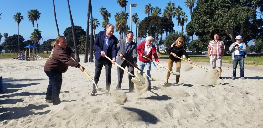 Sarah Mattinson (Area 6 Mission Beach Town Council rep), Mayor Kevin Faulconer, Andy Field (Parks and Rec Department assistant director), William Gardner (husband to the late Maruta Gardner) and Cordelia Mendoza (president of Mission Beach Women's Club) each shovel sand in the Bonita Cove Playground Groundbreaking Ceremony.