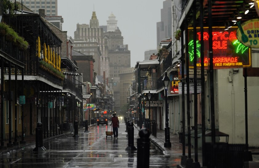 A man pulls a cart down a mostly deserted Bourbon Street in the French Quarter of New Orleans