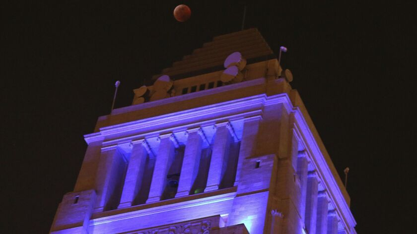 The moon hangs over Los Angeles City Hall on Jan. 20.